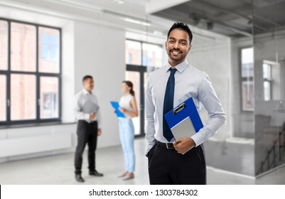 business, realty and people concept - smiling indian businessman or realtor with clipboard over empty office room background