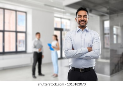 business, realty and people concept - smiling indian businessman or realtor over empty office room background