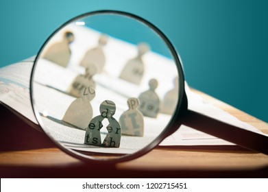 Business recruitment or hiring photo concept. Looking for talent. Icons of candidates are standing on open newspaper under magnifier.