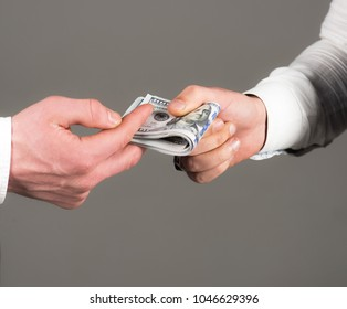 Business relations, getting salary, bribe, cash, black cash, profit, close up. Male clients hand pay, holds money in hand on grey background. Customer, client gives money. Payday and payment concept.