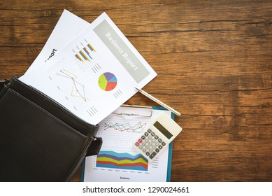 Business report chart preparing graphs on briefcase bag / Summary report in Statistics circle Pie chart on paper business document financial and calculator pen on the wooden table background