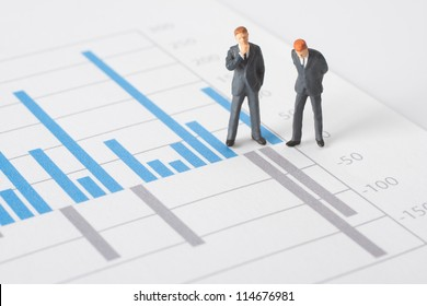 Business report, graph and business figurines illustrating profit decrease analyze.