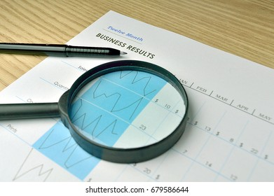 Business report on a wood tabletop with a pen and a magnifying glass
