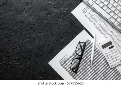 Business report preparing with calculator and glasses on dark office background top view mock up