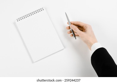Business and reporter topic: Hand of a businessman in a black suit holding a pen on a notebook on a white table