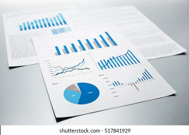 Business reports. Graphs and charts. Documents on gray reflection background.