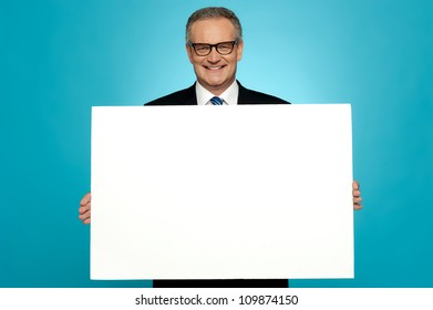 Business representative holding blank ad board and smiling at camera