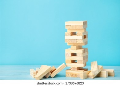 Business risk concept with wood jenga game. Wooden blocks on blue background