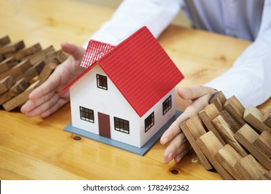 Business risk control Real estate concept,  Businessman protect wooden block fall to planning and strategy in risk estate to business Alternative and prevent. Investment Insurance Business.