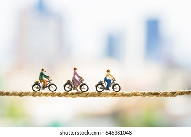 Business and risk management concept. Miniature people : Small figures cycling on rope with cityscape using as background.