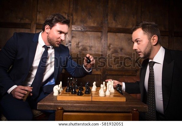 Business rivalry or competition concept. Two businessmen playing chess demonstrating competition between their offices. Business concept.