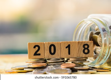 Business and saving money concept. 2018 NEW YEAR with piggy bank and pile of coins.