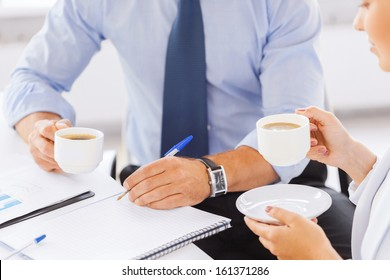 business, school and education concept - smiling businesswoman and businessman discussing something in office