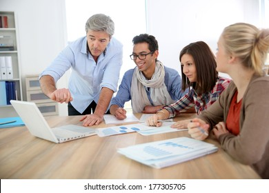 Business school students in marketing class with teacher