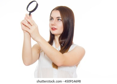 Business search concept. Concentrated business woman looking through magnifying glass.  isolated over white