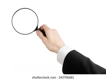 Business Search topic: businessman in a black suit holding a magnifying glass on a white isolated background