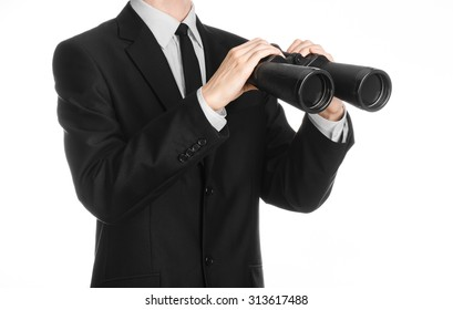 Business and search topic: Man in black suit holding a black binoculars in hand on white isolated background in studio
