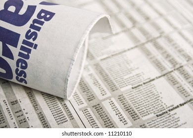 The business section of the newspaper rolled up and placed over a report of all stock and trading options. Please see my portfolio for more newspaper and finance images.