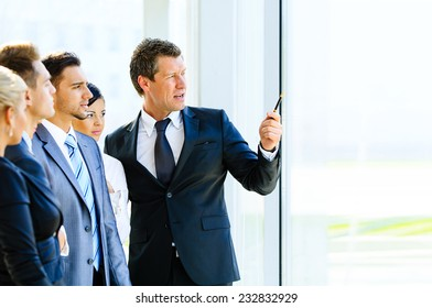 Business seminar where a boss explaining the company strategy to his colleagues