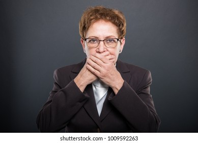 Business senior lady holding hand over mouth like not speaking on black background