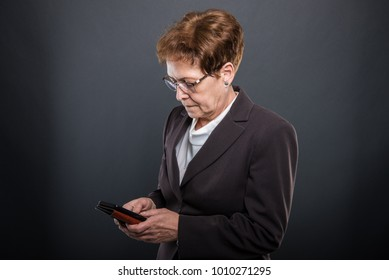 Business senior lady holding and texting on smartphone on black background