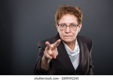 Business senior lady showing watching you gesture on black background with copyspace advertising area