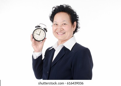 Business Senior woman holding alarm clock over white background