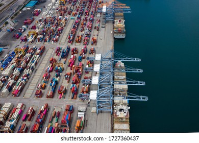 business service and industry shipping cargo containers transportation logistics by the sea and shipping port loading and unloading by crane and trailer aerial top view from drone camera