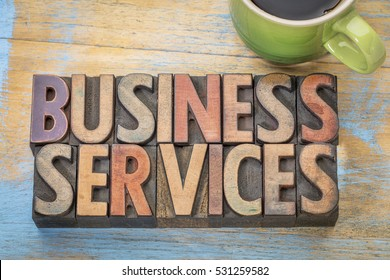 business services word abstract in letterpress wood type blocks with a cup of coffee