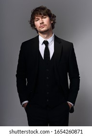 Business sexy man in black fashion suit posing on gray bacground with serious face. Closeup studio portrait