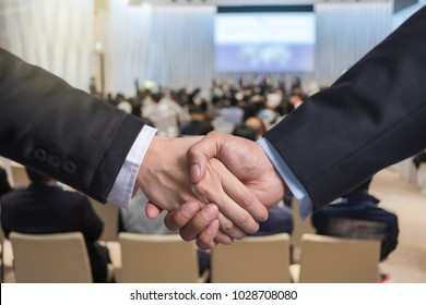 Business shaking hands of partner over the Abstract blurred photo of conference hall or seminar room with attendee background, business success and partnership concept
