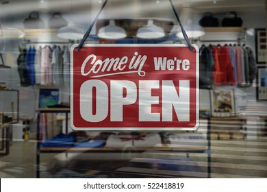 A business sign that says 'Come in We're Open' on clothing store window.