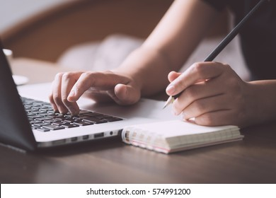 Business situation, female using laptop to get information and memo into paper