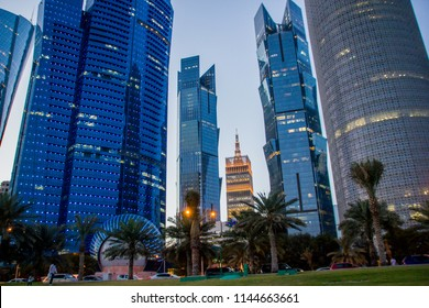 The business skyline of Doha with view from Corniche Road in Qatar in the evening with street lanterns. A new and modern state with a huge variety of buildings and offices