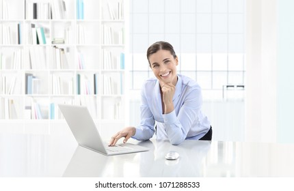 Business smiling woman or a clerk working at her office desk with computer, looking in camera, career and success concept