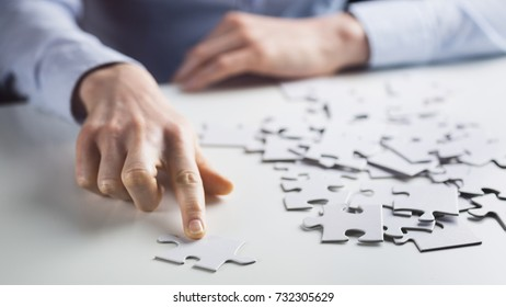 Business solution concept - female hand passing a jigsaw puzzle.