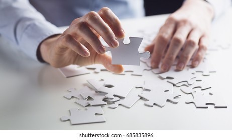 Business solution concept - hands holding a jigsaw puzzle.