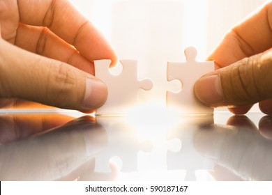 Business solutions, connections, success and strategy concept. Businessman hand connecting jigsaw puzzle.