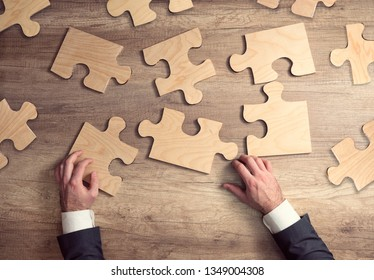 Business solutions, success and strategy concept. Businessman hand connecting jigsaw puzzle