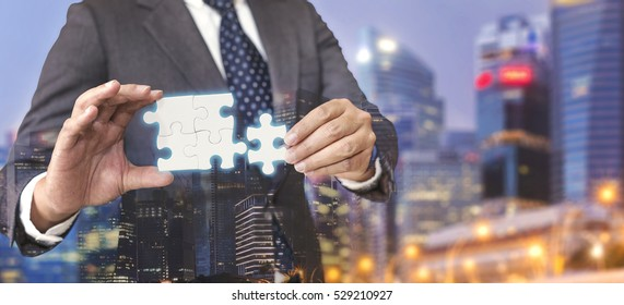 Business solutions, success and strategy concept. Businessman hand connecting jigsaw puzzle. Double exposure.