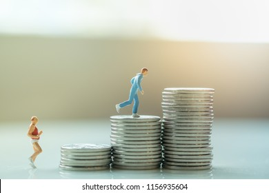 Business, sport and money concept. Two male runner miniature figure running on top of stack of silver coins.