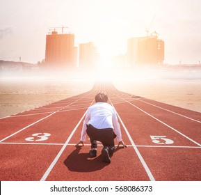 Business start competition on track. Rear view of worker kneeling on the start line to city building. Motivation and success business concept.