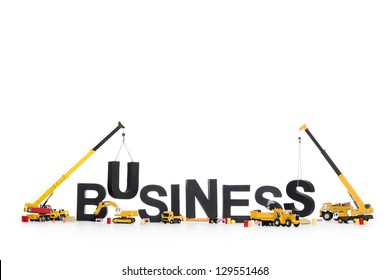 Business start up concept: Black alphabetic letters forming the word business being set up by group of construction machines, isolated on white background.