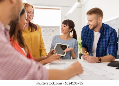 business, startup, architecture and people concept - happy international creative architect team or students with blueprint and tablet pc computer working at office