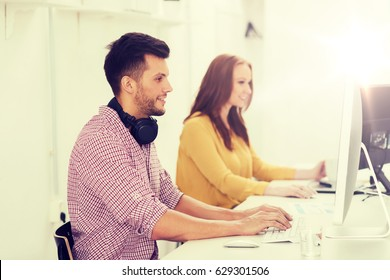 business, startup, education, technology and people concept - happy creative team or students with headphones and computer at office
