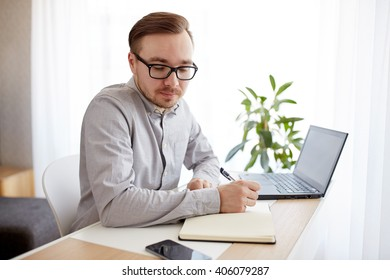 business, startup and people concept - businessman or creative male worker writing to notebook or diary and looking at smartphone at home office
