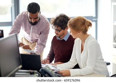 business, startup and people concept - creative team with papers and tablet pc computer in office