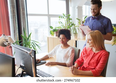 business, startup and people concept - happy creative team with computer and notebook in office