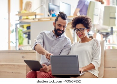 business, startup and people concept - happy creative team with laptop and tablet pc computer in office