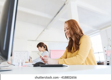 business, startup and people concept - happy businesswoman or creative worker texting on smartphone at office
